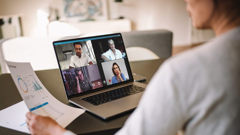 Office colleagues having a video call to discuss few financial reports. Business people working from home having a video conference. Over the shoulder view.